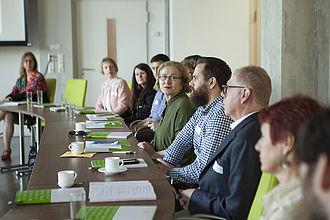 Mehrere Personen sitzen in einer Tischreihe. Eine der Personen scheint zu reden, die anderen zuzuhören.