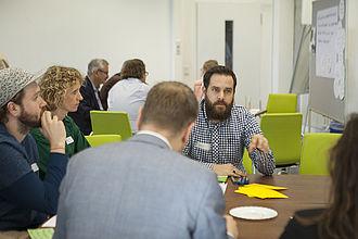 Fünf Personen sitzen an einem Tisch, eine Person redet, die anderen scheinen zuzuhören. Im Hintergrund ein weiterer Tisch mit Personen.
