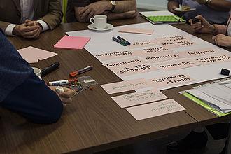 Fünf Personen sitzen an einem Tisch im Kreis und beschriften mit einem Filzstift Kärtchen. Die Gesichter der Personen sind nicht zu sehen.