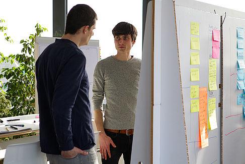 Zwei männliche Personen stehen vor einem Clipboard und scheinen sich zu unterhalten.