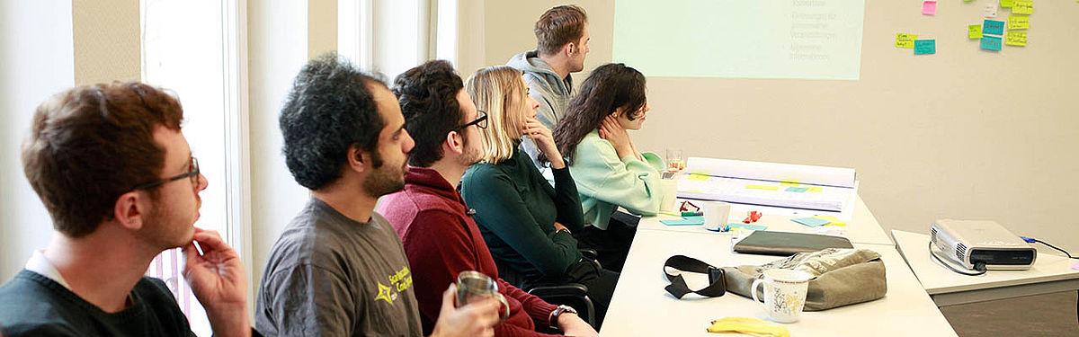 Sieben Personen sitzen an einer Tischreihe und scheinen einem Vortrag zuzuhören.