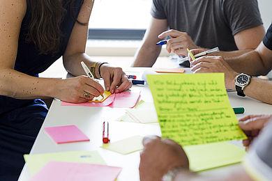 Vier Personen an einem Tisch hantieren mit Stiften und Zetteln.