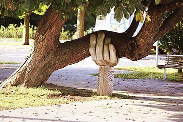 Baum der von einer aus Holz gefertigten Hand gestützt wird.