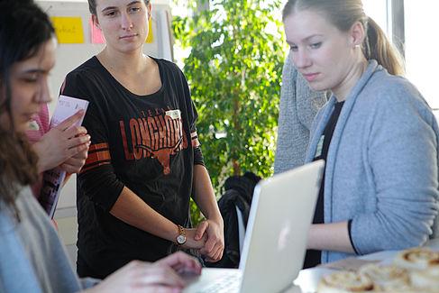 Vier weibliche Personen vor einem aufgeklappten Laptop.