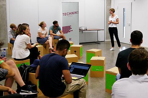 """Mehrere Personen sitzen auf Kartons, eine davon hat einen aufgeklappten Laptop. Eine Person steht davor und scheint einen Vortrag zu halten. Im Hintergrund ist ein Plakat auf dem """"Technik"""" steht."""