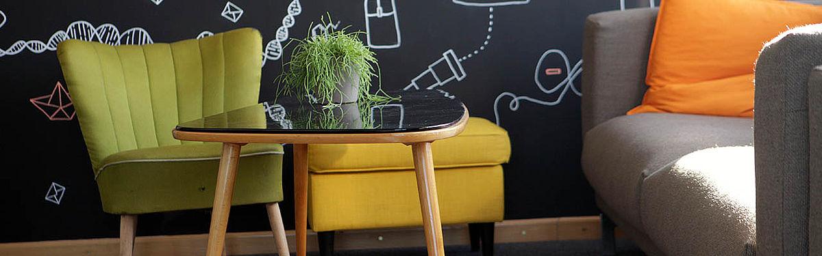 Tisch auf einem Teppich, daneben ein Sofa, ein Sessel und eine Fußablage.