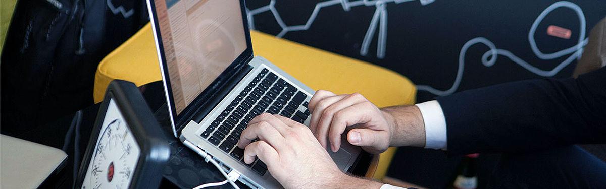 Eine Person an einem Laptop, es sind nur die Unterarme der Person zu sehen. Sie scheint einen Anzug zu tragen. Davor ist eine Stoppuhr zu sehen.