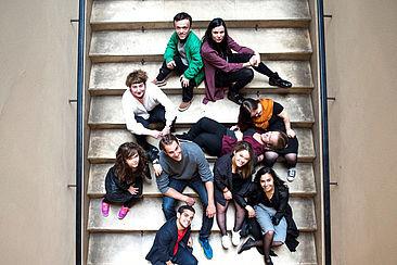 Zehn junge Erwachsene die auf einer Treppe sitzen.